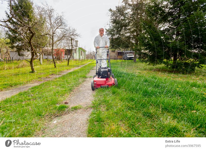 Farmer in protective clothing is mowing a lawn in a garden with a petrol lawn mower Backyard Bloom Botanic Botanical Care Clipper Cultivate Cut Cutter Early