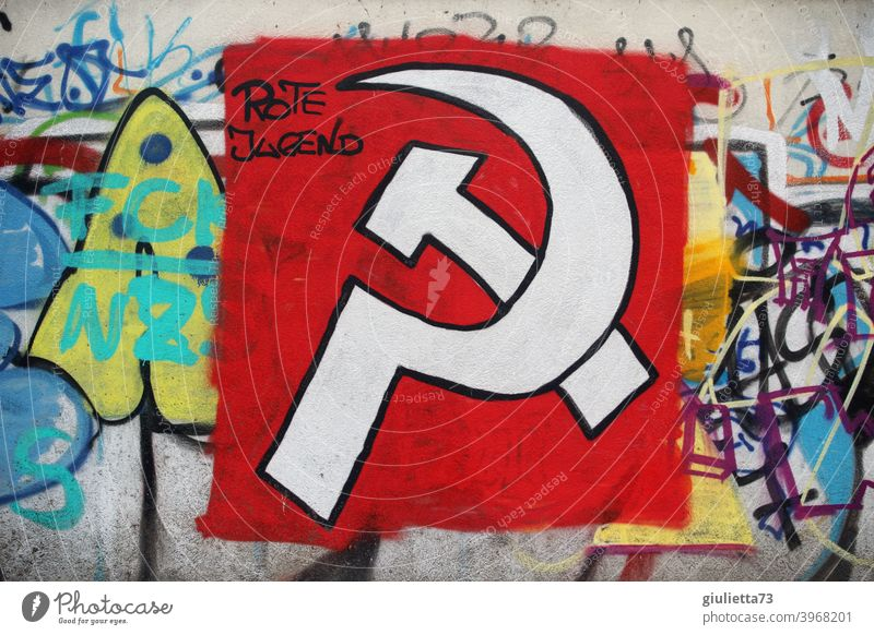 Graffiti | Hammer and sickle sprayed with white paint on a red background on a wall and supplemented with the words Red Youth graffiti Graph hammer and sickle