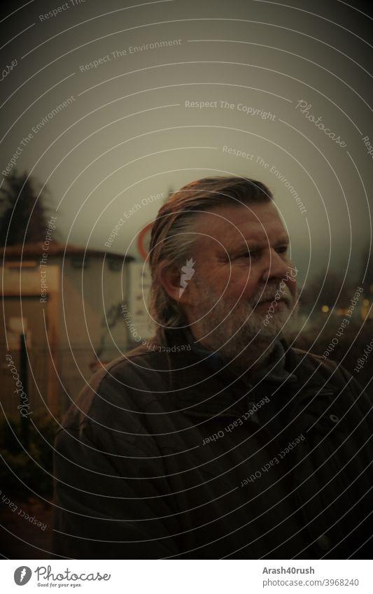 älterer Herr am Abend nachdenklich älterer Mann portrait bart kälte winter mann alter rentner outtdoor spazieren natur bewegung erholung nachdenken freizeit