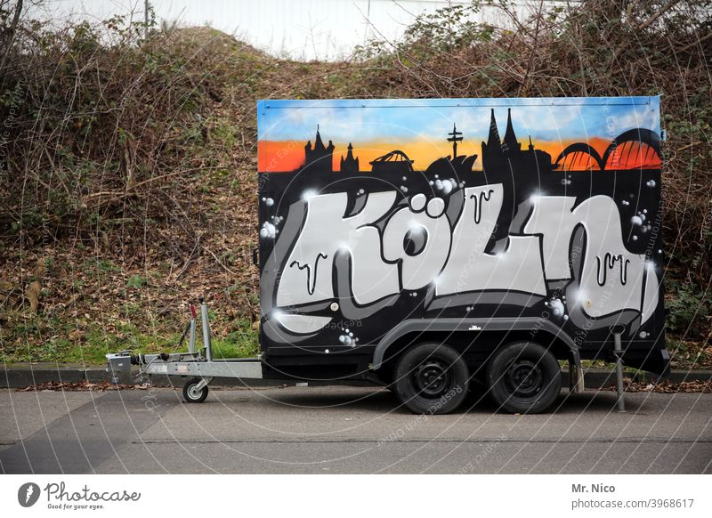 Trailer in Kölsch Logistics Means of transport Vehicle Mobility Trade Tire double axis Street turned off graffiti Cologne Characters Parking City panorama