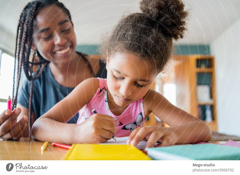 A father helping her daughter with homeschool. mother homework student learning lifestyle quarantine family children people lock down indoor motherhood