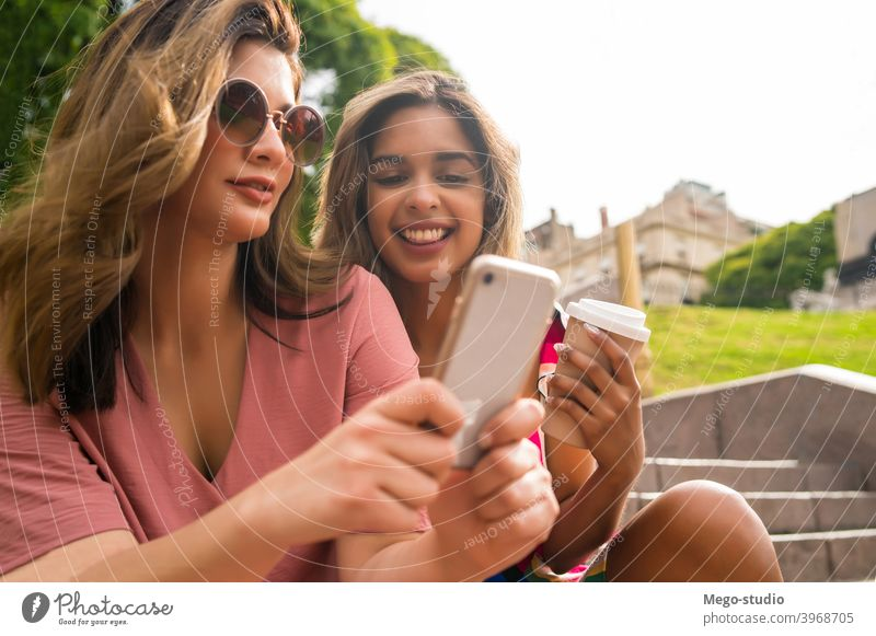 Two friends using mobile phone outdoors. two young smiling laughing friendship lifestyle leisure talking fun women cellular communicate app enjoying network
