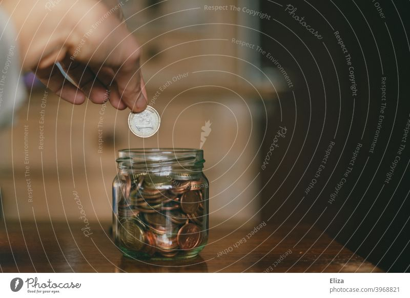 A hand throws a euro into a jar full of coins. Saving. Coin Save Money Hand Bird's-eye view Glass Money box Euro Loose change Coins stop small livestock