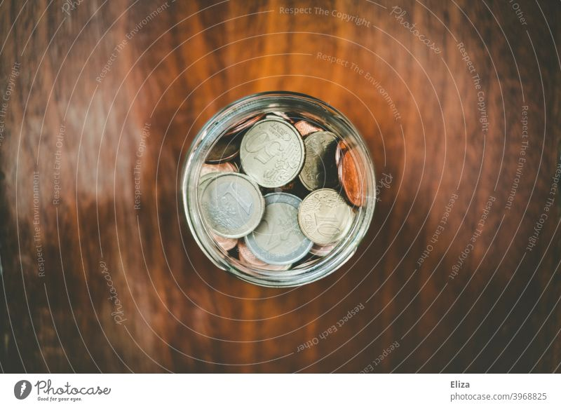 A jar full of saved coins. Coin Save Money Hand Bird's-eye view Glass Money box Euro Loose change Coins stop small livestock small change Wood safekeeping