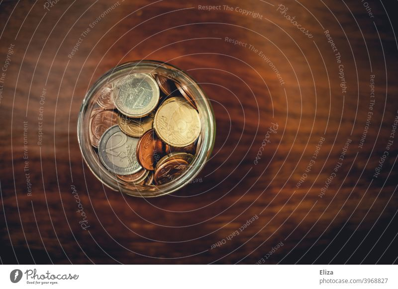 A jar full of saved coins Coin Save Money Hand Bird's-eye view Glass Money box Euro Loose change Coins small livestock Wood Thrifty amass small change financing
