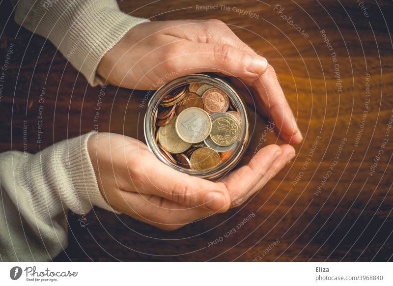 Hands holding a jar full of coins. Saving. Coin Save Money Bird's-eye view Glass Money box Euro Loose change Coins stop small livestock small change Wood assets