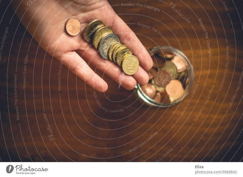 A person puts money coins in a jar. Saving. Coin Save Money Hand Bird's-eye view Glass Money box Euro Loose change Coins stop small livestock small change Wood