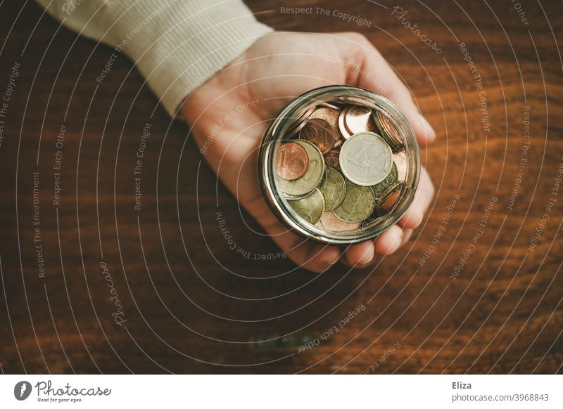 One hand holds a jar full of coins. Saving. Coin Save Money Hand Bird's-eye view Glass Money box Euro Loose change Coins stop small livestock small change Wood