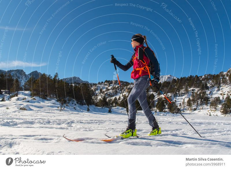 Woman in the mountains practicing mountain skiing in the Pyrenees of Andorra in 2021. active adrenaline adventure alpinist championship climb climber climbing