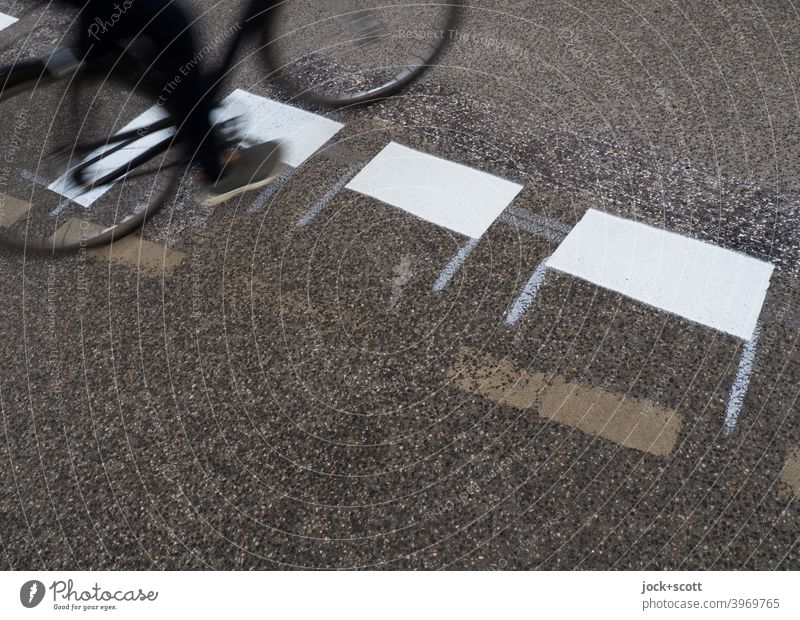 Cyclist rides over freshly painted road markings Lane markings Traffic infrastructure Asphalt Street Road sign New Traffic cone Dashed line Mobility cyclist