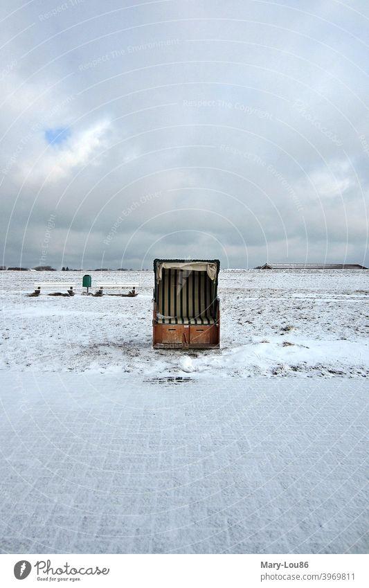 Single beach chair in snow against cloudy sky Beach chair Snow Ocean Island Deserted Copy Space top Copy Space bottom Copy Space left Copy Space right