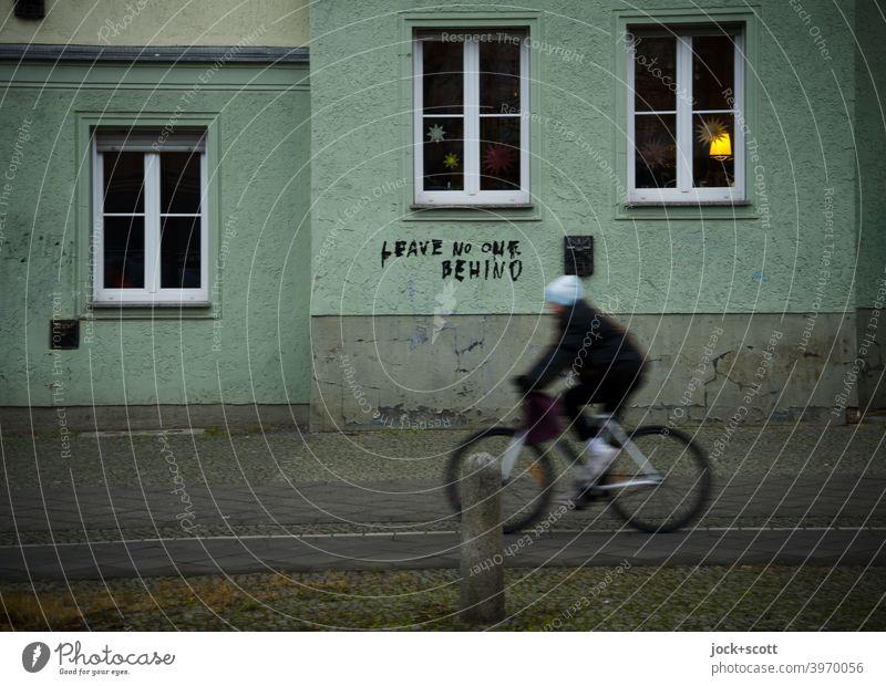 LEAVE NO ONE BEHIND cyclist Cycle path Sidewalk Winter's day Berlin Prenzlauer Berg Schönhauser Allee motion blur Mobility Authentic mountain bike Facade Window