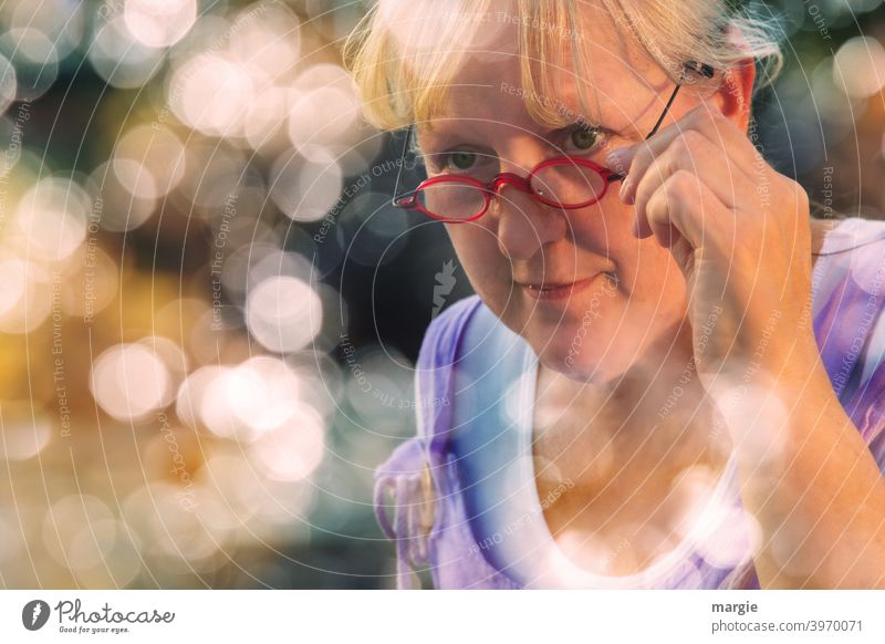 AST10 l A sympathetic woman looks over her glasses, holds them tightly and smiles slightly. She is framed with many lens lights Woman Smiling kind