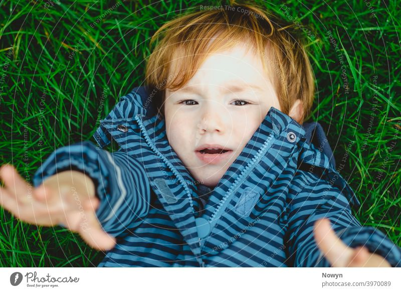 Don't leave me, Mummy! Young boy lying on the ground looking up with outstretched arms blue casual closeup cool face ginger gjeans gras head shot headshot
