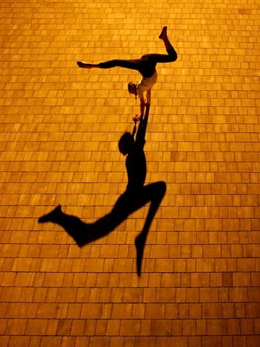 Gymnast at night with shadow Shadow Light Structures and shapes Contrast Exterior shot Gymnastics Colour photo Handstand Splits contorsion Movement