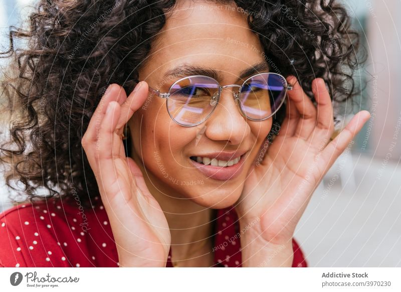 Cheerful young woman in eyeglasses style trendy fashion smile cheerful happy modern ethnic female adjust curly hair lady lifestyle positive spectacle content