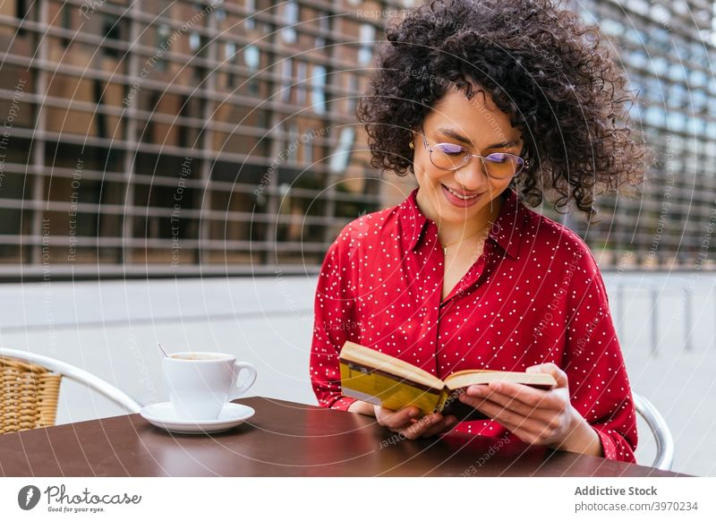 Happy woman reading book on cafe terrace happy coffee rest enjoy young positive ethnic curly hair hispanic female eyeglasses interesting lifestyle free time