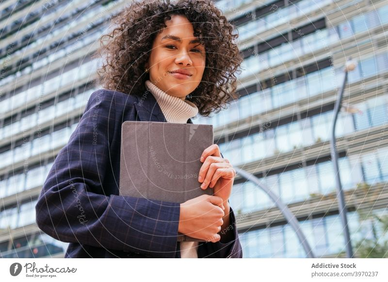 Businesswoman holding tablet on city street businesswoman using urban young formal browsing digital contemporary positive ethnic female curly hair modern