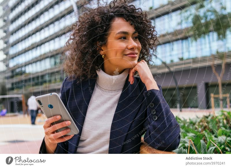 Happy businesswoman on smartphone on street speak mobile phone confident smile young ethnic female entrepreneur elegant urban lifestyle device gadget