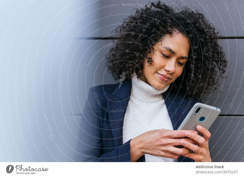 Young ethnic woman browsing smartphone businesswoman using mobile gadget young communicate online read positive curly hair device connection cellphone internet