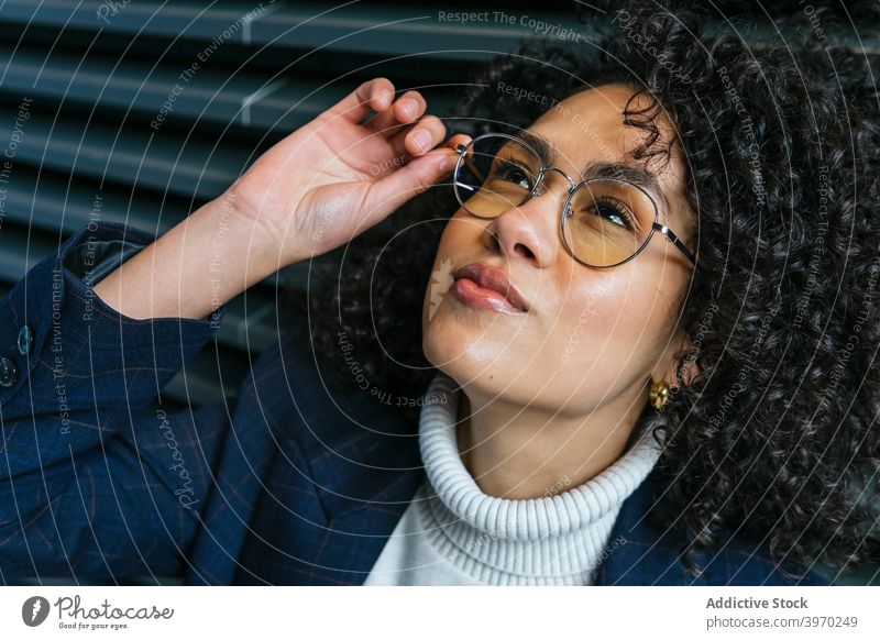 Confident ethnic businesswoman in eyeglasses confident self assured style trendy serious fashion young spectacle eyewear personality touch adjust modern