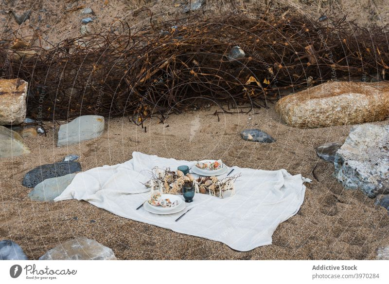 Picnic set on blanket on sandy beach picnic romantic food decoration seashore nature white summer coast vacation holiday relax recreation celebrate couple rest