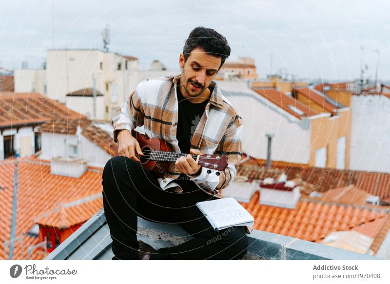 Man with ukulele composing music on rooftop man play instrument compose melody song acoustic male ethnic building concentrate guitar perform musician guitarist