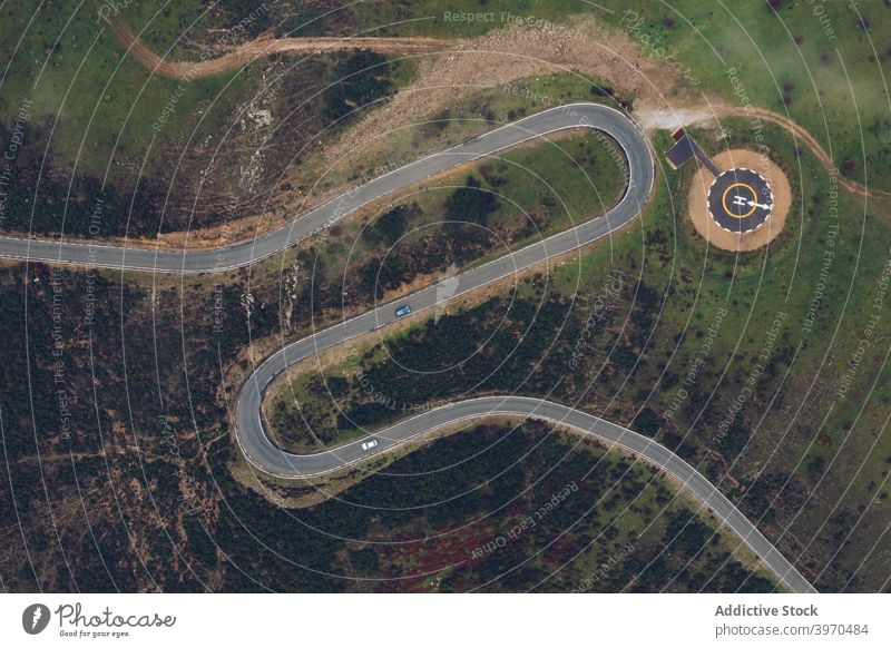 Modern round helipad in green suburbs road curve mountain landscape highland picturesque terrain nature scenery scenic hill valley idyllic destination