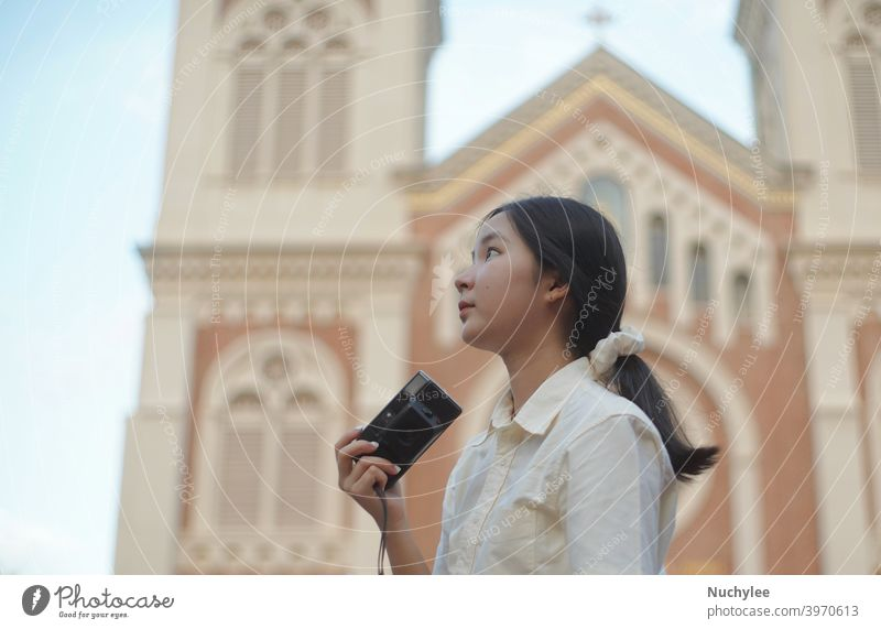 Young asian millennial teen girl using camera during traveling in the street and church background, teenager and travel concept attractive beautiful casual