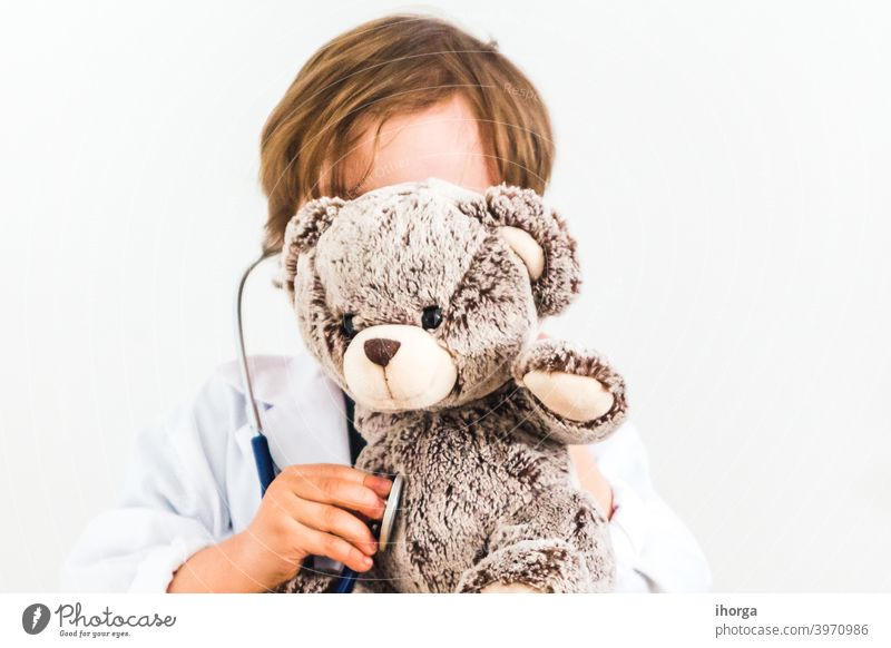 boy dressed as doctor auscultating teddy bear on white background adorable baby care cheerful child childhood clinic clothes concepts cute examining fantasy