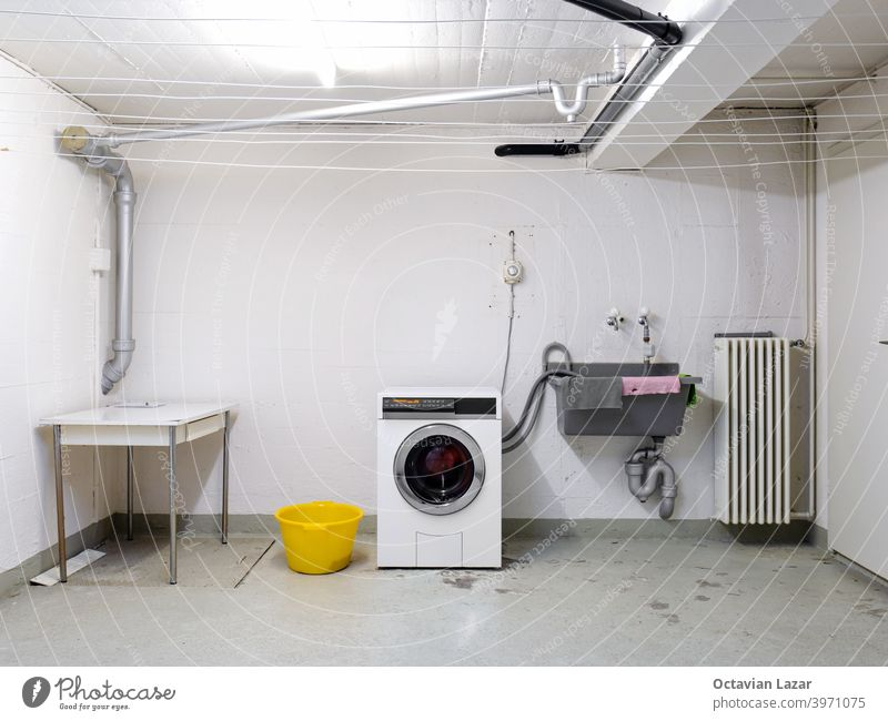 Shared apartment building laundry room with washing machine in used wash sink and piping wide angle view public hoses washer water sink laundromat machinery