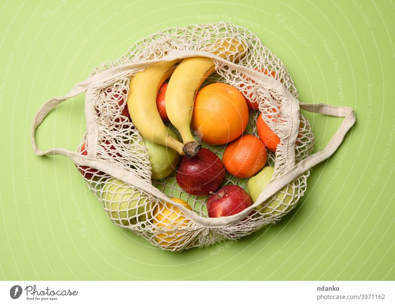 ripe fresh fruits in a textile string bag on a green background, top view mesh healthy natural reusable organic food vegetarian market shopping vegan eco