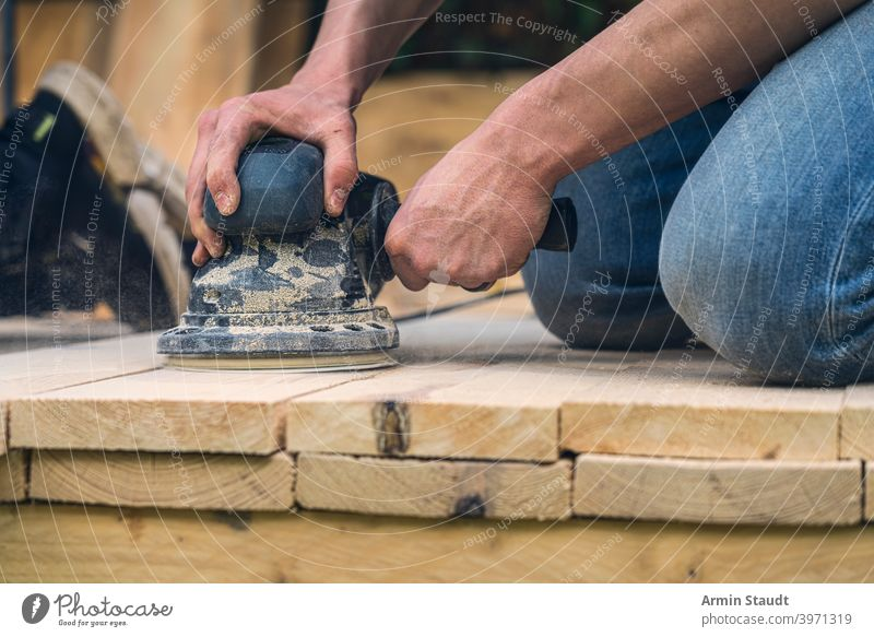 close up of a worker sanding wood planks with a grinder machine knees hand arm working closeup dust grinding tool equipment carpenter craft construction sander