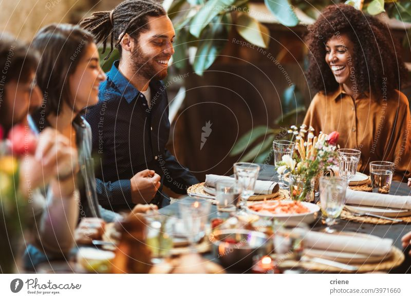 happy group of friends sitting at table having dinner together Adult Candid Outdoor Young Adult alcohol backyard celebrating chatting dinner party diversity