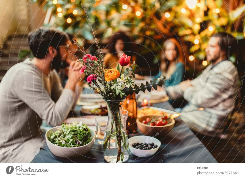 friends at dinner table with flowers and food Adult Candid Outdoor Young Adult alcohol backyard celebrating chatting dinner party diversity drinking eating
