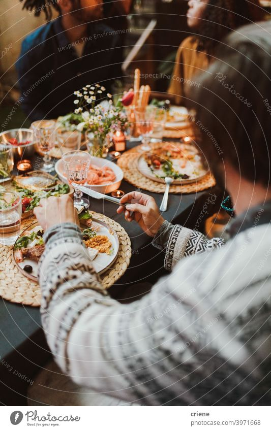 Group of friends eating food and having fun at dinner party together Adult Candid Outdoor Young Adult alcohol backyard bread celebrating chatting diversity