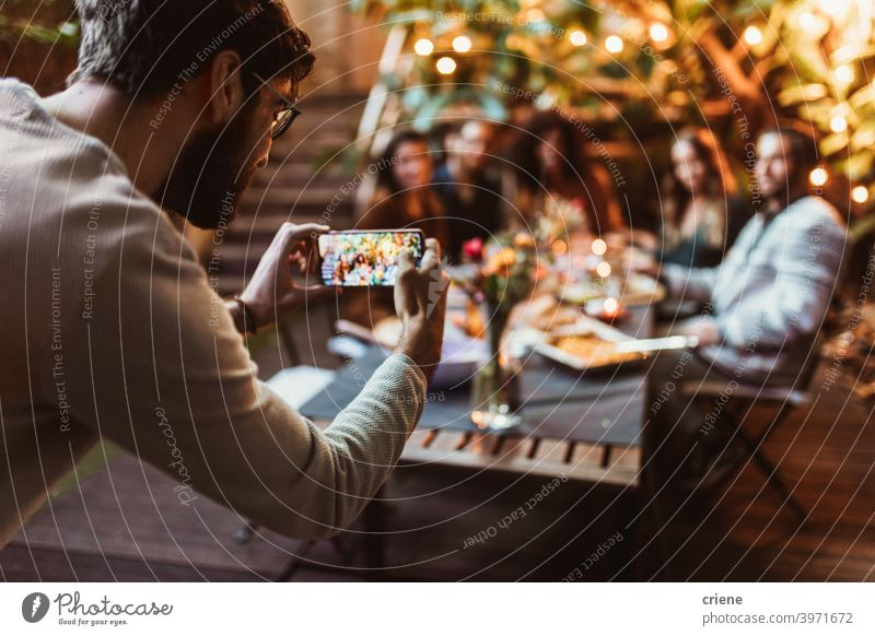 young adult taking photo of his friends with phone at dinner party Adult Candid Outdoor Smartphone Young Adult alcohol backyard celebrating chatting diversity
