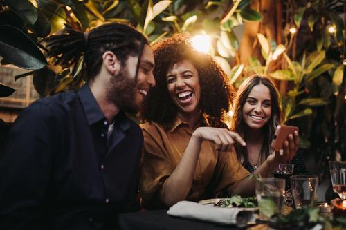 Young adult friends laughing and having fun at dinner party with phone Candid Happiness Smartphone Smiling Young Adult african american african ethnicity