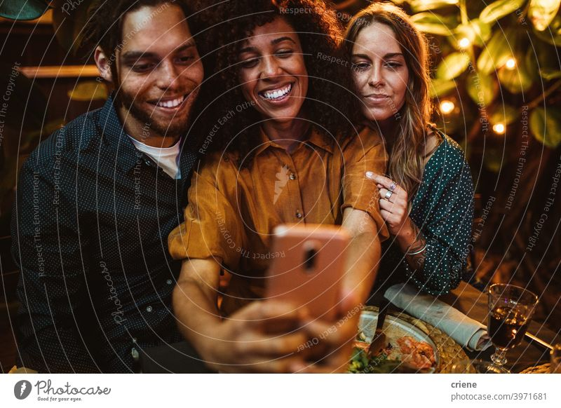mixed race group of young adult friends taking selfie with phone at party Candid Happiness Smartphone Smiling Young Adult african american african ethnicity