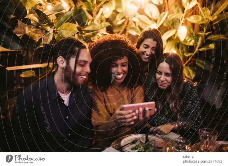 Group of young adult friends looking at phone having fun at party Candid Happiness Smartphone Smiling Young Adult african american african ethnicity caucasian
