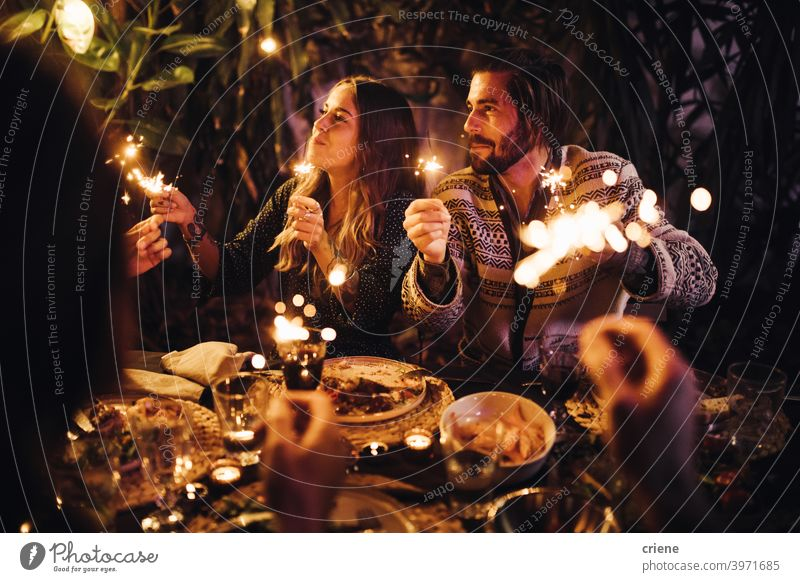 Young adult couple celebrating with sparklers at dinner party together 4th of july Candid Dating Happiness Heterosexual Couple People Smiling Young Adult