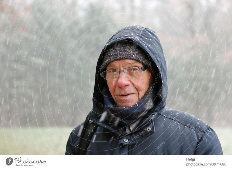 Portrait of senior standing in snow flurry with winter jacket, scarf, hat and hood Human being Man Senior citizen portrait Face Cap Scarf Hooded (clothing)