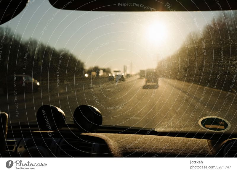 Through the dirty windshield of a car you can see the highway and the blinding sun Highway Driving In transit mobile Mobility road trip Car Street Transport