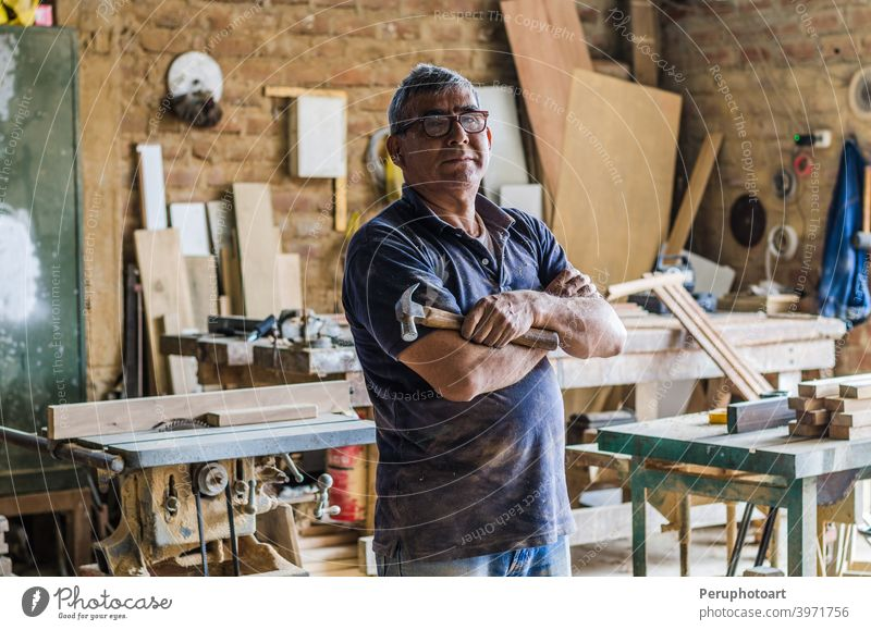 Portrait of senior carpenter in his workshop and looking at camera. carpentry craftsman male occupation people portrait working industry old plank standing