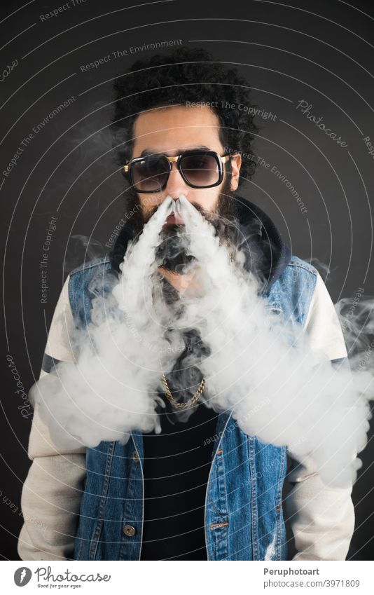 Young man vaping, studio shot. Bearded guy with sunglasses blowing a cloud of smoke on black background. Concept of smoking and steam without nicotine. beard