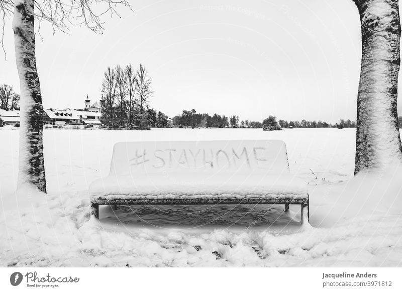 Bank in the snow with hashtag Stay home Snow Bench Stayhome Stay at home stay home writing Landscape trees stay at home Quarantine guard sb./sth. Corona virus