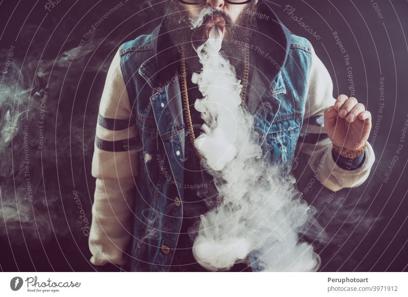 Young man with beard throwing a cloud of steam. Black background. Vaping an electronic cigarette vape vaping smoke adult cool lifestyle person smoker habit