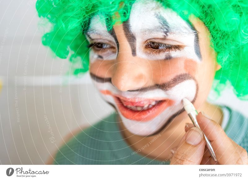Mother painting her son's face like a clown art boy brush carnival caucasian celebration child childhood circus close up color colorful costume cute face paint
