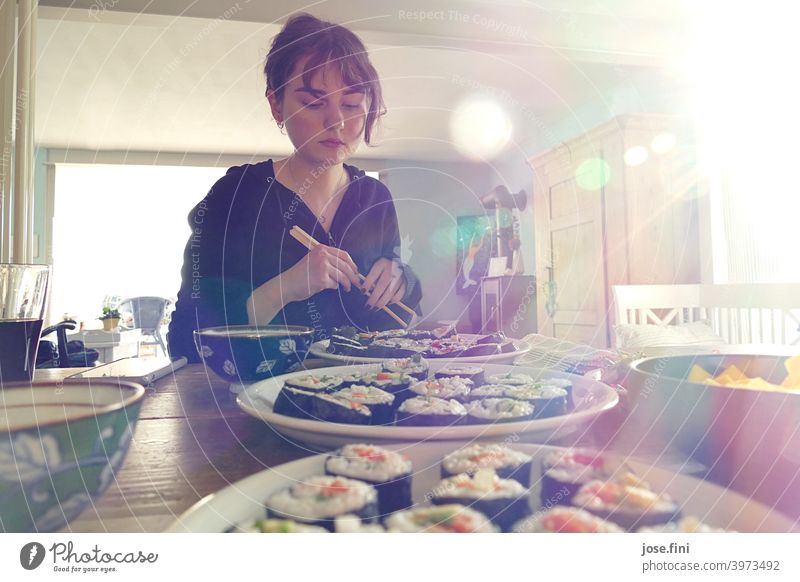 Young woman sitting with chopsticks at a table with sushi. Woman young adult teenager Student Lifestyle person Sushi Self-made Food Food Photography Vegetable