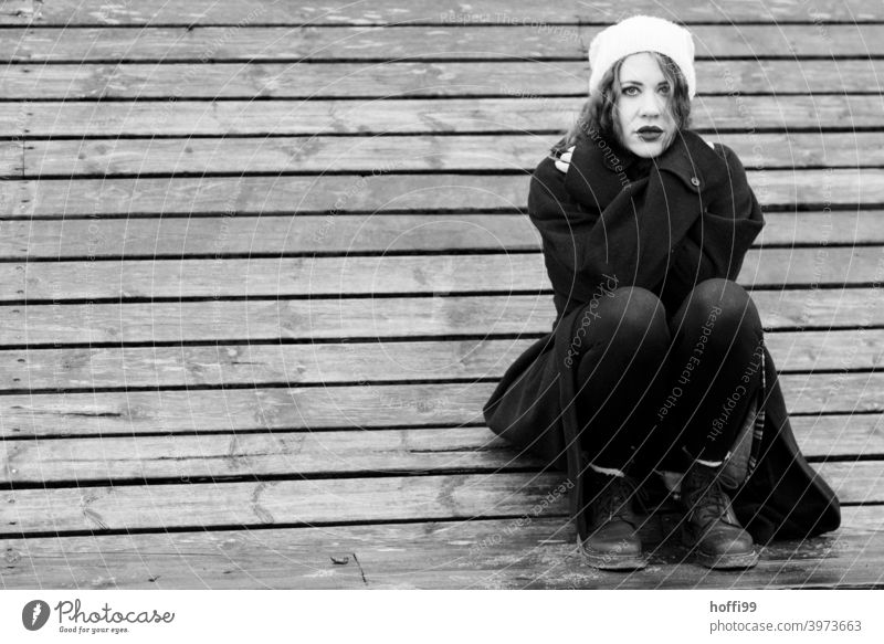 the young woman squats on a bench and looks into the camera Woman crossed arms Coat Looking into the camera long coat portrait Lifestyle Authentic pretty